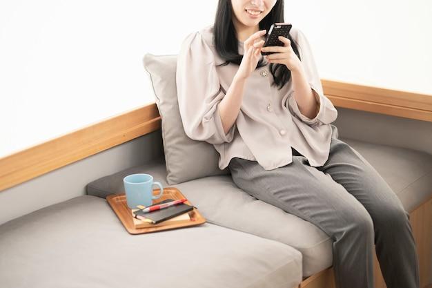 아시아 여자 앉아서 집에서 스마트 폰을 운영