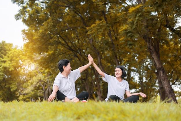 아침에 함께 공원에 앉아 휴식을 취하는 아시아 여성, 행복하고 웃고, 긍정적인 생각, 건강 및 생활 방식 개념