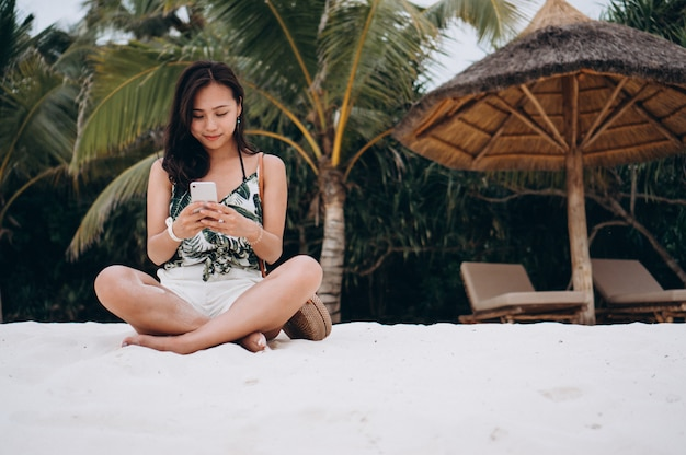 Asian woman sitting at the beach and using phone