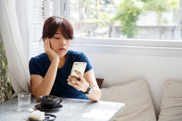 Asian woman sitting in cafe and waiting notification message on her smartphone