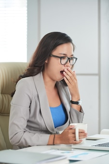 Asian woman sitting at desk in office with mug and yawning