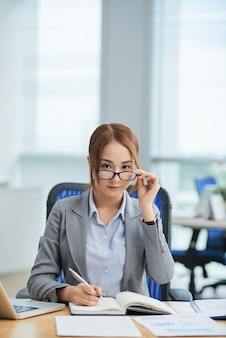 Asian woman sitting at desk in office, writing in planner and looking ahead above glasses