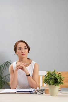 Asian woman sitting at desk with journal, looking away and thinking