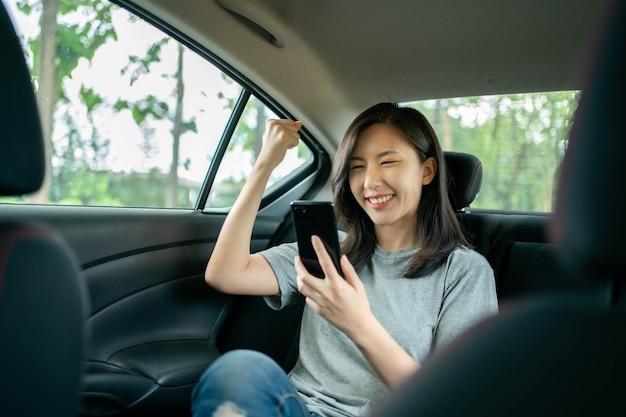 차에 앉아있는 아시아 여성은 그녀의 휴대 전화에서 메시지를 본 후 기뻐합니다.