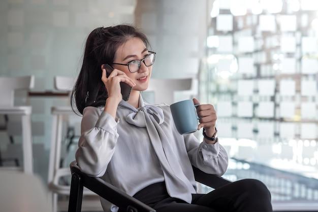 Азиатская женщина, сидящая в кресле, расслабляется в офисе, разговаривает по телефону и пьет кофе.