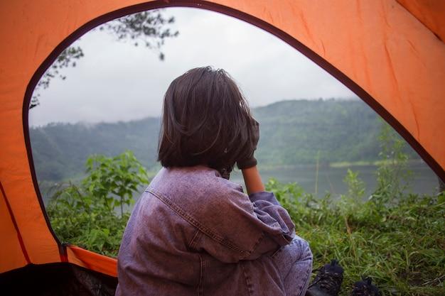 テントに座って、キャンプ休暇で日没時に山の湖の景色を見ているアジアの女性
