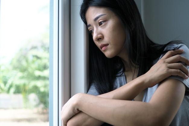 Азиатская женщина сидит внутри дома, глядя в окно. женщина смущена, разочарована, грустна и расстроена