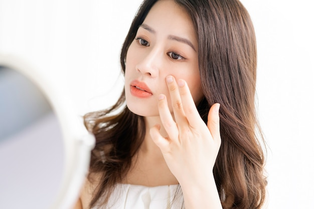 鏡の前で化粧を座っているアジアの女性
