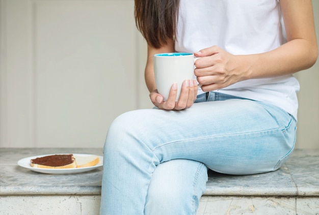 Asian woman sitting on marble chair in front of house for have breakfast in the morning