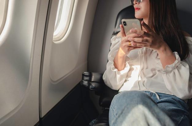 飛行機の窓の近くに座って、飛行中に携帯電話を使用しているアジアの女性は外を見ました