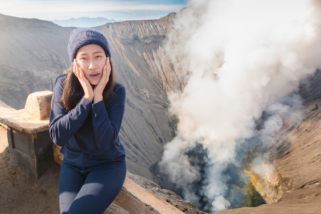 Asian woman sitting near volcano crater with erupting smoke.