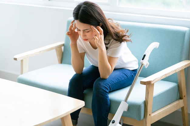 집을 청소하는 동안 피곤한 표정으로 의자에 앉아 아시아 여자