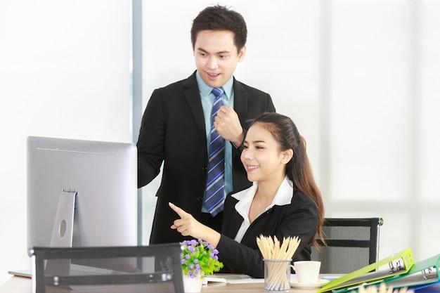 책상에 앉아 데스크탑 컴퓨터를 가리키는 아시아 여성과 사무실에서 즐겁게 일하는 사업가. 작업에 대 한 개념 회의 팀입니다.