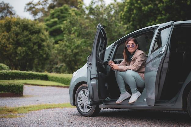 Азиатская женщина, сидящая на компактном легковом автомобиле