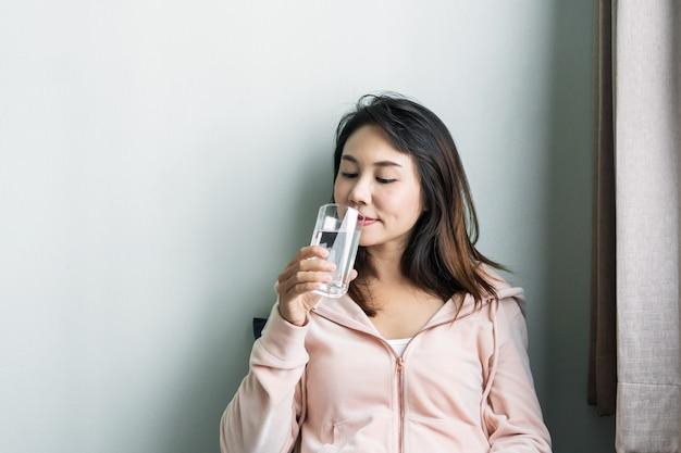 Азиатская женщина сидит на диване и пьет воду утром