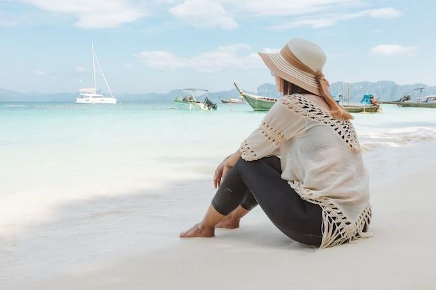 素晴らしい海を眺め、休暇中に美しい自然を楽しみながらビーチに座っているアジアの女性。夏休みのコンセプト。
