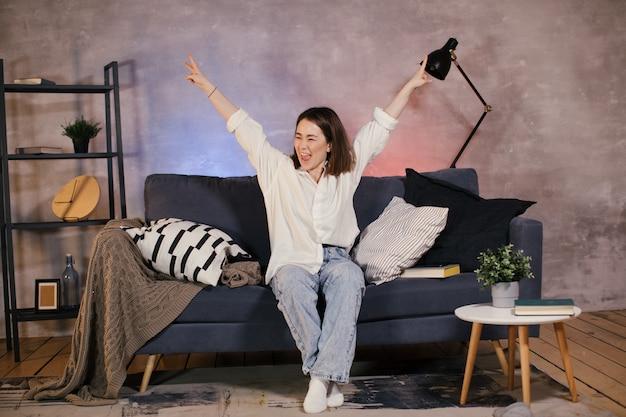 Азиатская женщина сидит на диване и смотрит телевизор, и она смешная