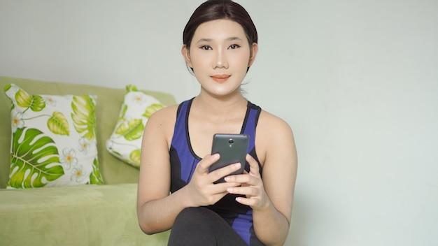 집에서 요가를 마친 후 편안하게 앉아 휴대폰을 하고 있는 아시아 여성