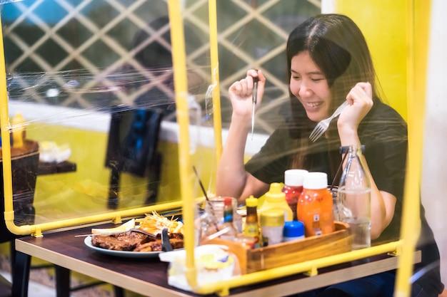 ステーキレストランで自己隔離し、テーブルシールドを持っている食事を楽しむアジアの女性
