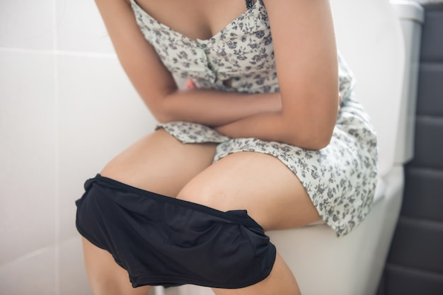 Asian woman sitting on toilet in the bathroom and holding her painful stomach of bad stoma
