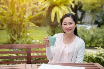 アジアの女性が自宅の庭で一杯のコーヒーと座っています。