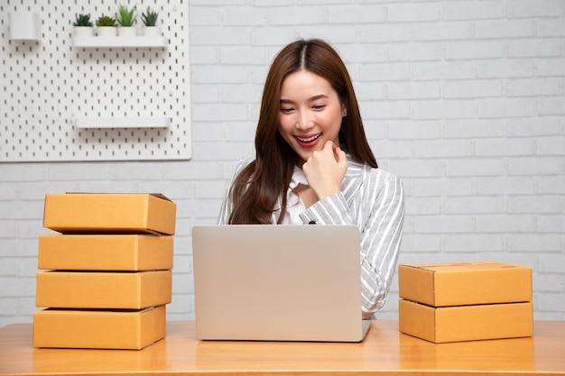 Азиатская женщина сидит с коробкой и компьютерным ноутбуком на деревянном столе в гостиной дома