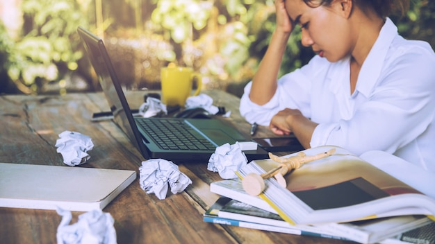 Asian woman sitting working stressed