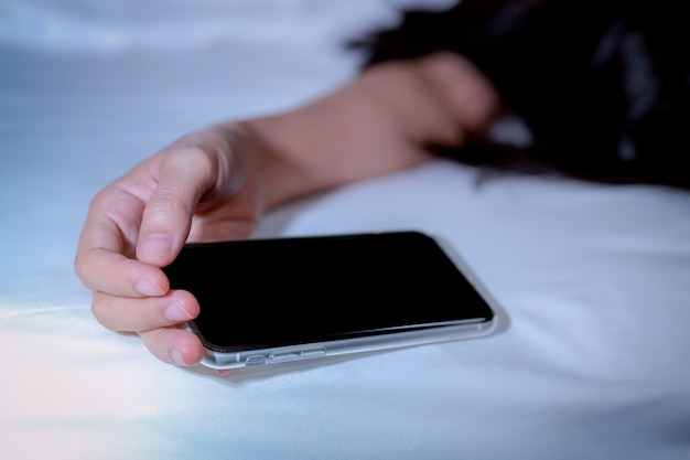 Asian woman sleeping in bed at home and hand holding mobile phone. woman using smartphone in bedroom.
