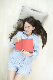 Asian woman sleeping on the floor while holding a book at home.