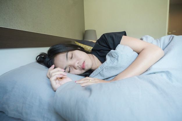 Asian woman sleeping on gray bed in the bedroom.