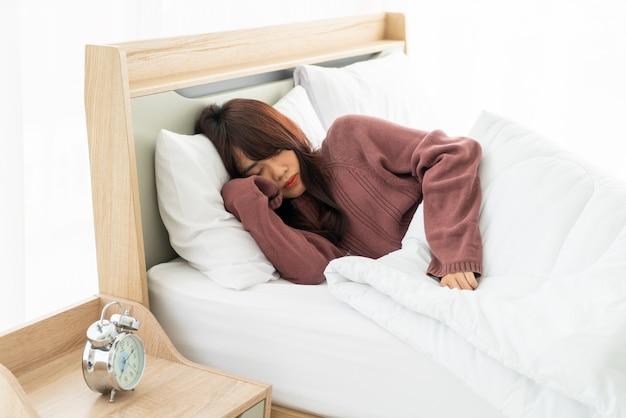 Азиатская женщина спит на кровати утром