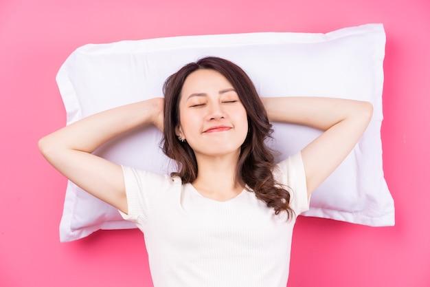 ピンクで寝ているアジアの女性