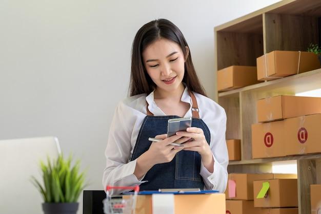 スマートフォンを持ってオフィスの机に置かれた小包箱をオンラインで販売するアジアの女性中小企業の所有者。