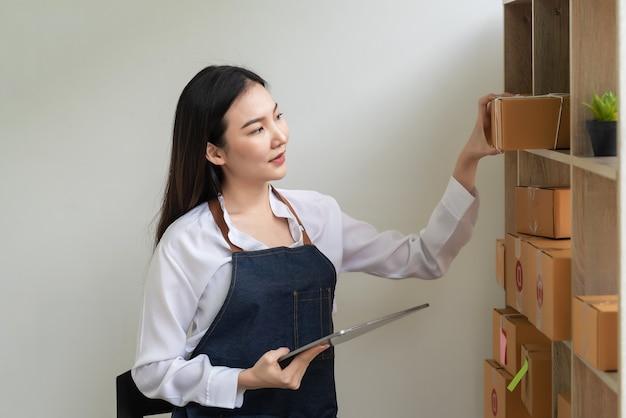 自宅で顧客に配達する前に小包をチェックするためにタブレットを持っているアジアの女性中小企業の所有者。