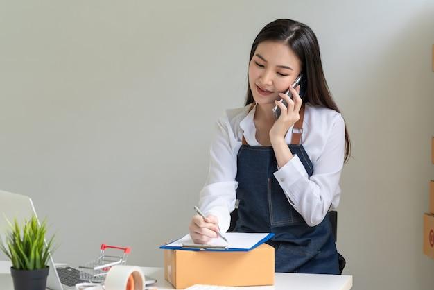 아시아 여성 소기업 소유자는 고객과 전화 통화를 하고 집에서 온라인 판매 아이디어를 메모합니다.