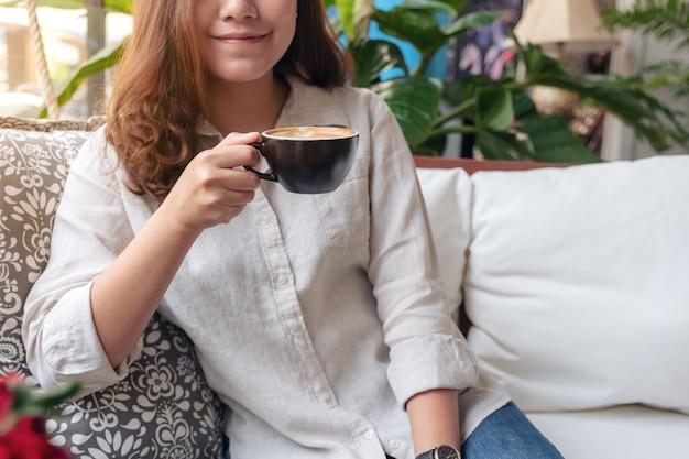 カフェで気持ちよくホットコーヒーの香りと飲み物を飲むアジアの女性
