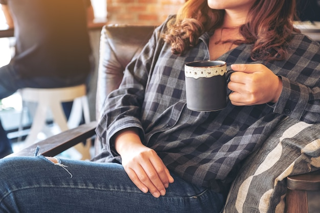 Asian woman smelling and drinking hot coffee with feeling good in cafe