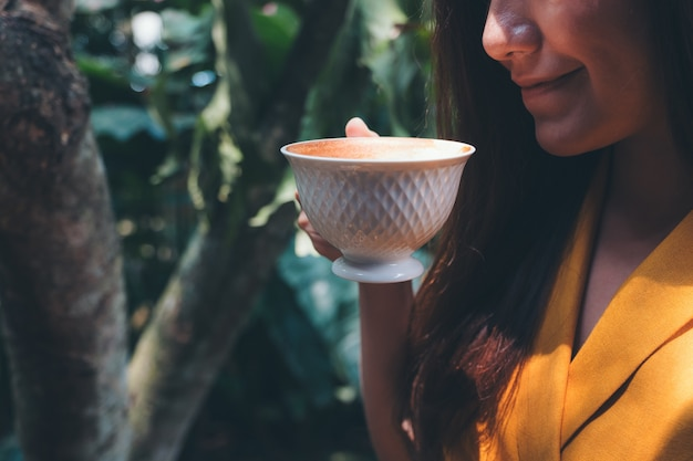 Asian woman smelling and drinking hot coffee with green nature background