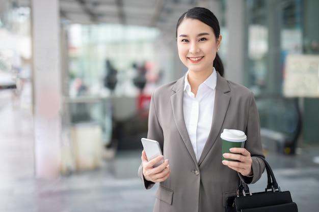 흐릿한 건물 배경을 배경으로 스마트폰을 들고 미소 짓는 아시아 여성