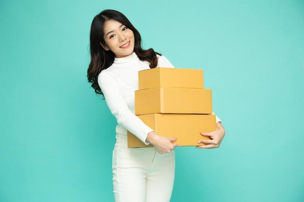 녹색 배경에 격리된 소포 상자를 들고 웃고 있는 아시아 여성