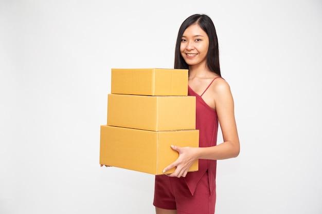 흰색 배경에 격리된 소포 상자를 들고 웃고 있는 아시아 여성