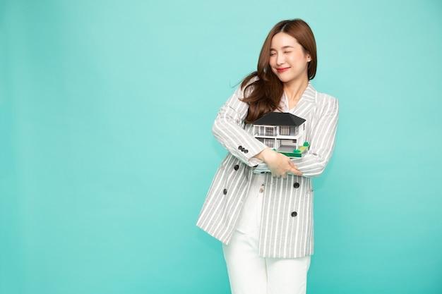 아시아 여자 미소와 포옹 꿈의 집 샘플 모델은 녹색 배경 위에 절연