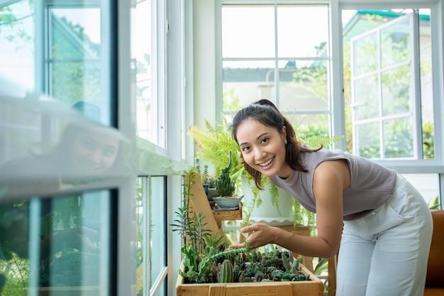 아시아 여자 웃 고 집에서 하루 휴식을 위해 정원에서 식물을 찾고.