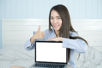 Asian woman smiling and showing blank laptop computer screen in her bedroom.