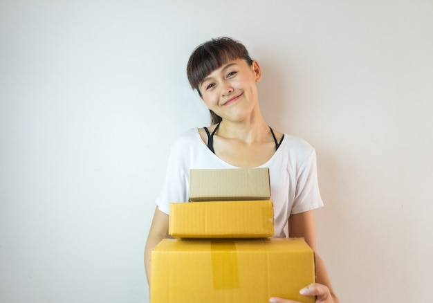 Asian woman smiling carrying three cardboard boxes. startup small business concept