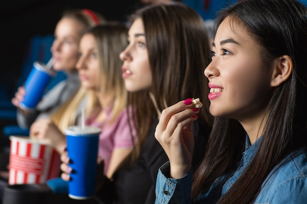 Азиатская женщина, весело улыбаясь, ест попкорн, смотрит фильмы со своими подругами