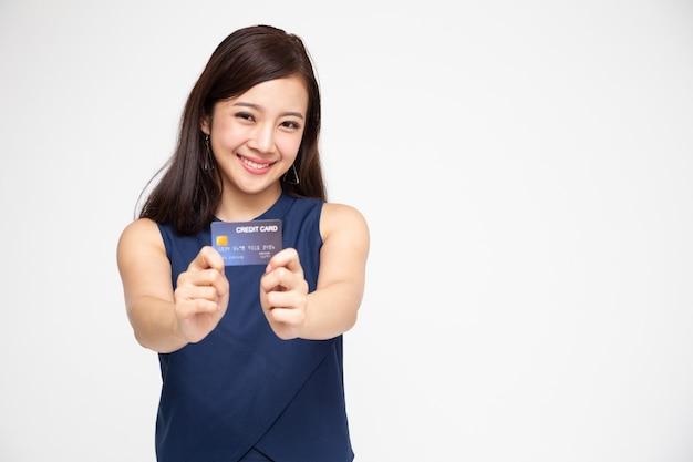 Азиатская женщина улыбается кредитной картой для оплаты или оплаты онлайн-бизнеса.