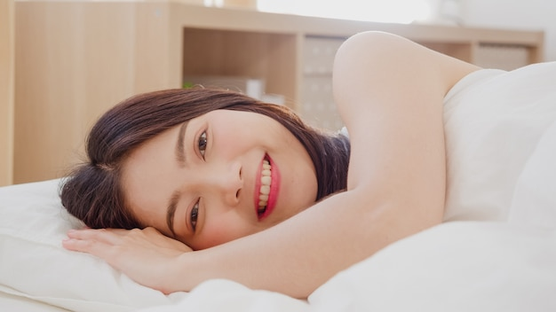 Asian woman smiling lying on bed in bedroom