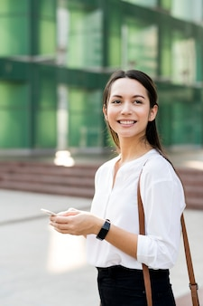 Asian woman smiling and playing on phone