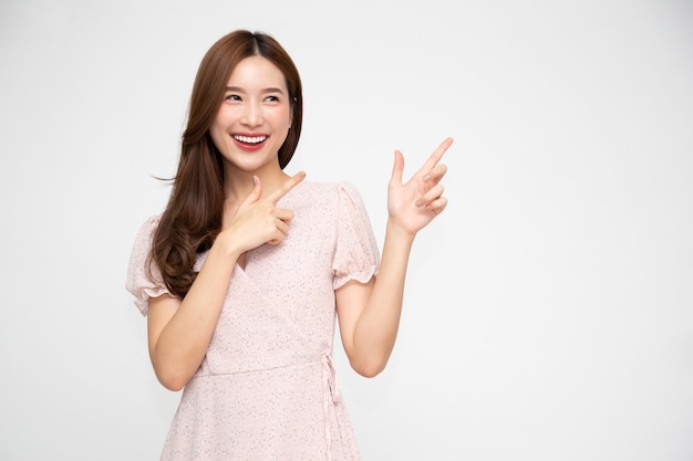 Asian woman smiling and pointing to empty copy space isolated on white wall